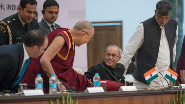 His Holiness the Dalai Lama talking to President of India Pranab Mukherjee as he takes his seat at the start of the Laureates and Leaders for Children Summit in New Delhi, India on December 10, 2016. Photo/Tenzin Choejor/OHHDL