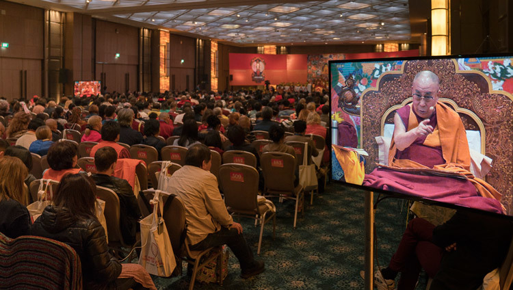 People in the back of the hall watching His Holiness the Dalai Lama on TV screens during his teaching in Delhi, India on December 25, 2016. Photo/Tenzin Choejor/OHHDL