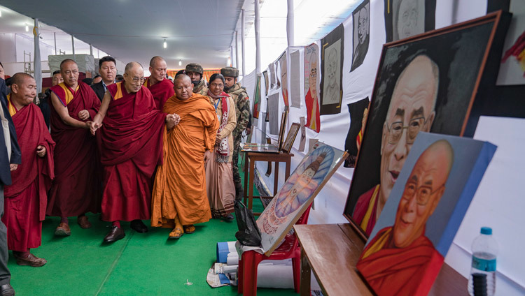 His Holiness the Dalai Lama looking at results of a student competition to portray him as he arrives at the Kalachakra teaching ground in Bodhgaya, Bihar, India on December 31, 2016. Photo/Tenzin Choejor/OHHDL