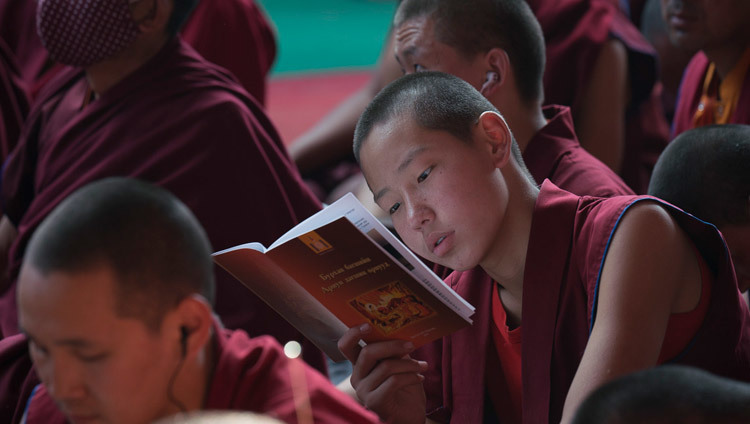 A young monk following the text during His Holiness the Dalai Lama's teachings preliminary to the Kalachakra Empowerment in Bodhgaya, Bihar, India on January 5, 2017. Photo/Tenzin Choejor/OHHDL