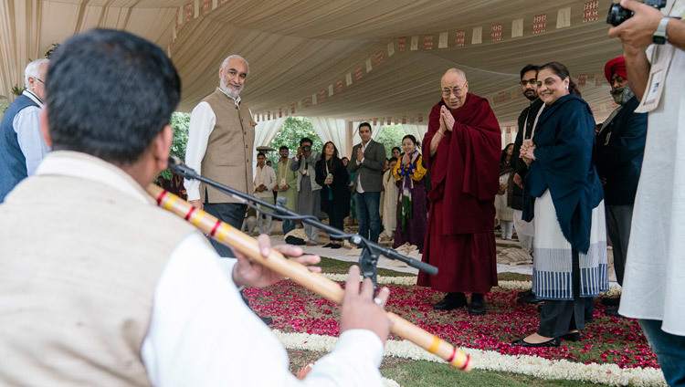 His Holiness the Dalai Lama taking a moment to listen to a flute player as he arrives at the start of the second day of the Vidyaloke teachings in New Delhi, India on February 4, 2017. Photo/Tenzin Choejor/OHHDL