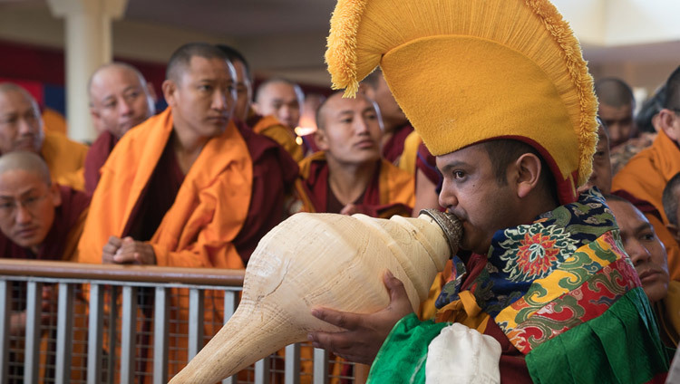 A monk playing a traditional horn escorting His Holiness the Dalai Lama to the the teaching throne at the Tsuglagkhang courtyard in Dharamsala, HP, India on March 12, 2017. Photo by Tenzin Choejor/OHHDL