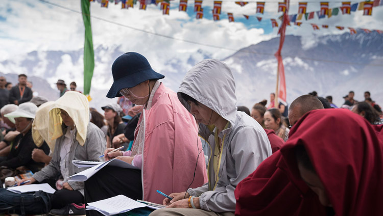 Members of the audience following the text as His Holiness the Dalai Lama continues his teaching on 'Thirty-seven Practices' in Disket, Nubra Valley, J&K, India on July 13, 2017. Photo by Tenzin Choejor/OHHDL