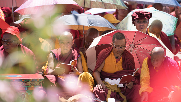 """Protecting themselves from the sun with umbrellas, monks in the crowd following the text as His Holiness the Dalai Lama reads from 'A Guide to the Bodhisattva's Way of Life"""" on the first day of his teachings in Leh, Ladakh, J&K, India on July 28, 2017. Photo by Tenzin Choejor/OHHDL"""
