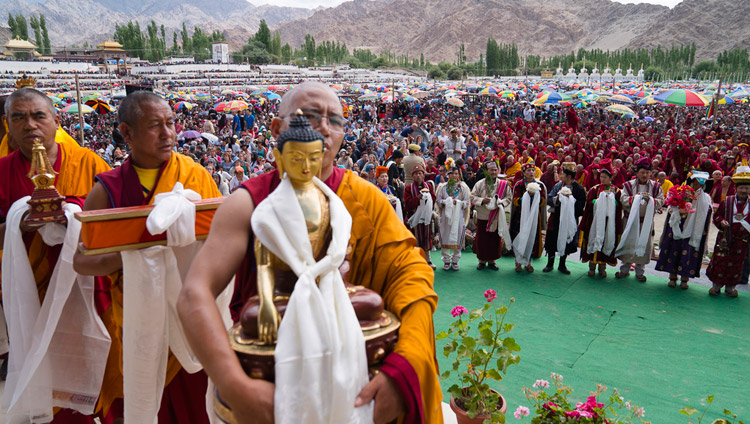 Members of the community carrying offerings pass in front of His Holiness the Dalai Lama while local artists perform behind them during the Long-Life Offering ceremony in Leh, Ladakh, J&K, India on July 30, 2017. Photo by Tenzin Choejor/OHHDL