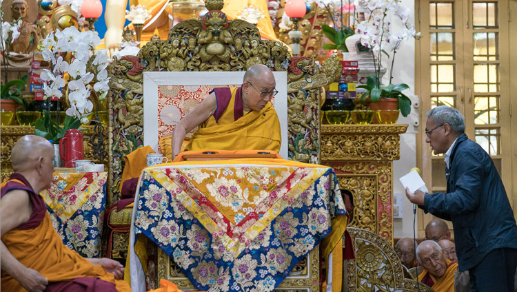 The English interpreter reading questions from the audience during a break in His Holiness the Dalai Lama's teaching at the Tsuglagkang in Dharamsala, HP, India on August 29, 2017. Photo by Tenzin Phuntsok/OHHD