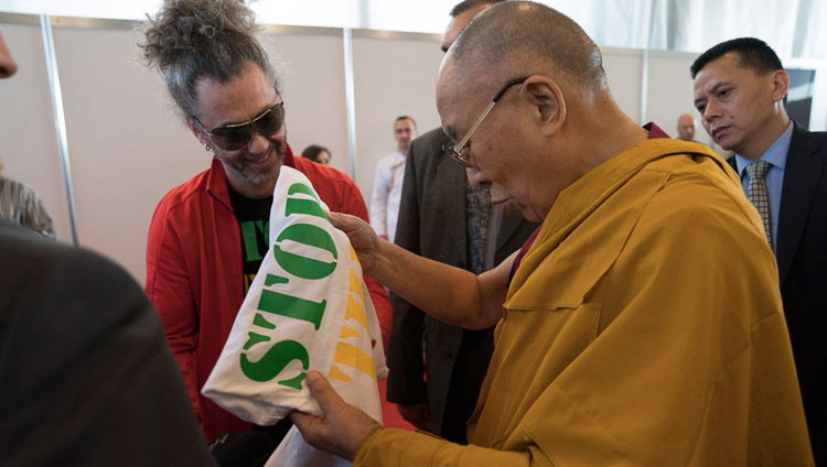 His Holiness the Dalai Lama looking at a t-shirt offered by Latvian singer Horens Stalbe after his meeting with Tibet supporters from the Baltic States in Riga, Latvia on September 24, 2017. Photo by Tenzin Choejor