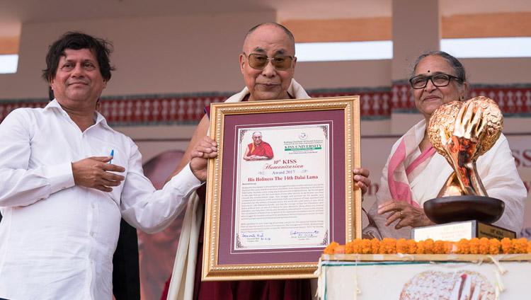 His Holiness the Dalai Lama holding the KISS Humanitarian Award presented to him at KISS University in Bhubaneswar, Odisha, India on November 21, 2017. Photo by Tenzin Choejor