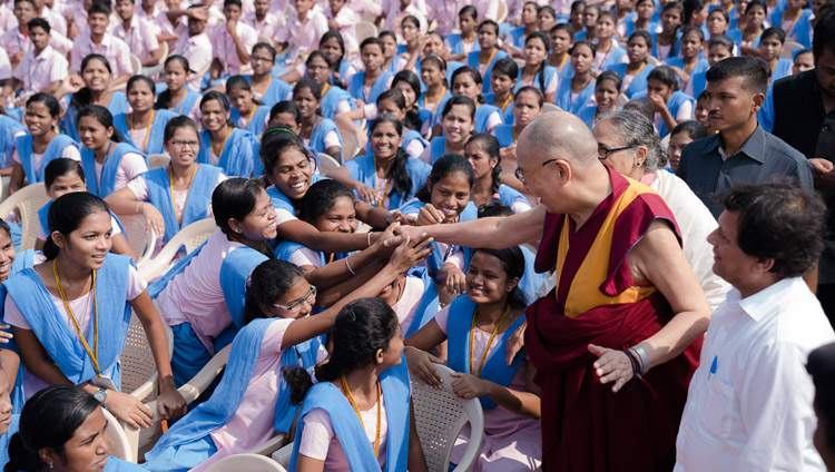 His Holiness the Dalai Lama reaching out to some of the more than 25,000 students gathered at KISS University for the KISS Humanitarian Award presentation in Bhubaneswar, Odisha, India on November 21, 2017. Photo by Tenzin Choejor