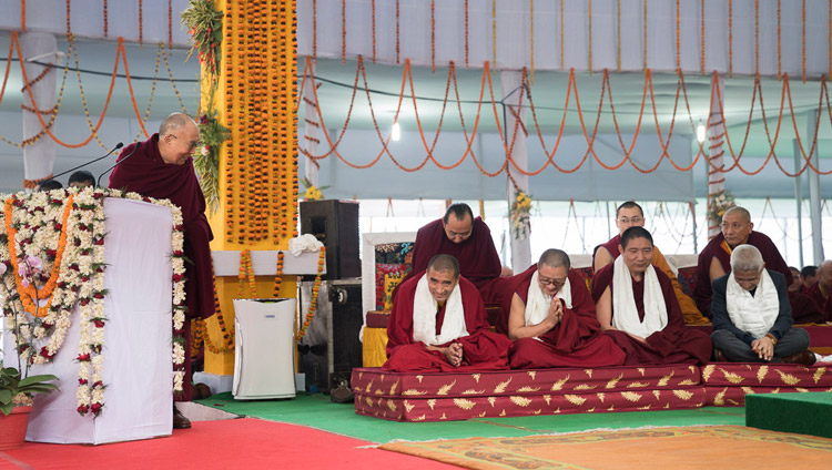 "His Holiness the Dalai Lama thanking the Geshes who undertook the research work for the original compilation in Tibetan during the release ceremony for ""Science and Philosophy in the Indian Buddhist Classics, Vol. 1: The Physical World"" in Bodhgaya, Bihar, India on January 7, 2018. Photo by Lobsang Tsering"