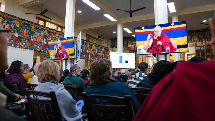 Some of the over 300 guests attending the Mind & Life Conference watching His Holiness the Dalai Lama on TV screens at the Main Tibetan Temple in Dharamsala, HP, India on March 14, 2018. Photo by Tenzin Choejor