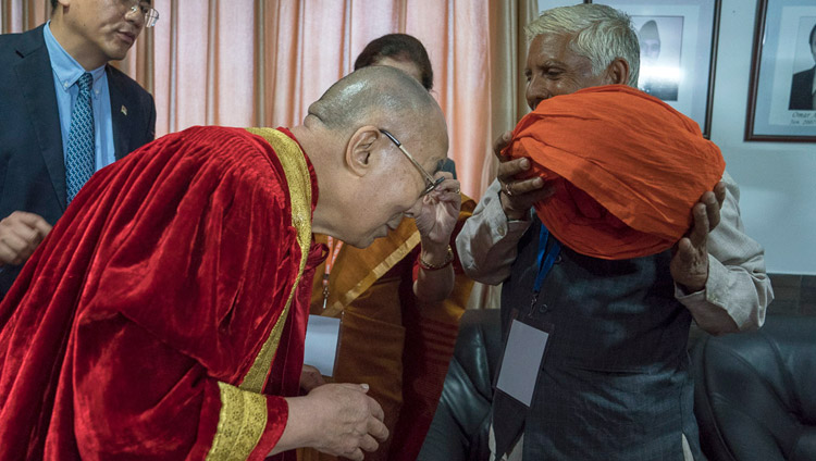 His Holiness the Dalai Lama putting on academic robes before proceeding to the First Convocation of the Central University of Jammu in Jammu, J&K, India on March 18, 2018. Photo by Tenzin Choejor