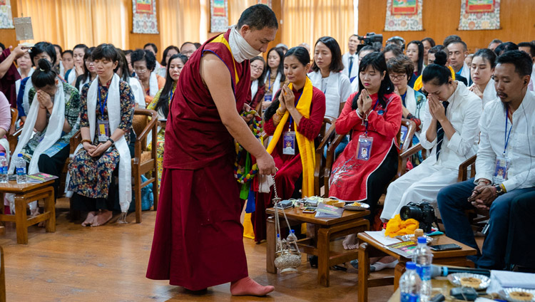 An assistant performing ritual cleansing with incense as His Holiness the Dalai lama gives the White Manjushri Permission on the second day of his meeting with groups from Vietnam at his residence in Dharamsala, HP, India on May 22, 2018. Photo by Tenzin Choejor