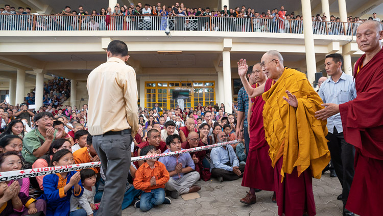 His Holiness the Dalai Lama waving to members of the audience sitting in the Main Tibetan Temple courtyard as he returns to his residence at conclusion his teachings for young Tibetan students at the Main Tibetan Temple in Dharamsala, HP, India on June 8, 2018. Photo by Tenzin Choejor