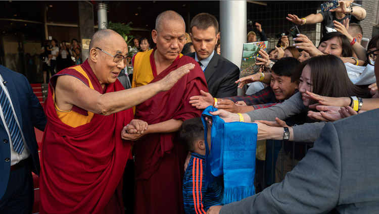 His Holiness the Dalai Lama greeting well wishers as he leaves his hotel on the way to Skonto Hall in Riga, Latvia on June 17, 2018. Photo by Tenzin Choejor