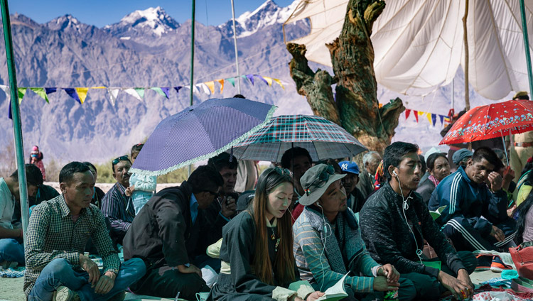 Mountains rise up from Nubra Valley in the background as members of the audience listen to His Holiness the Dalai Lama's teaching at Samstanling Monastery in Sumur, Nubra Valley, Ladakh, J&K, India on July 16, 2018. Photo by Tenzin Choejor
