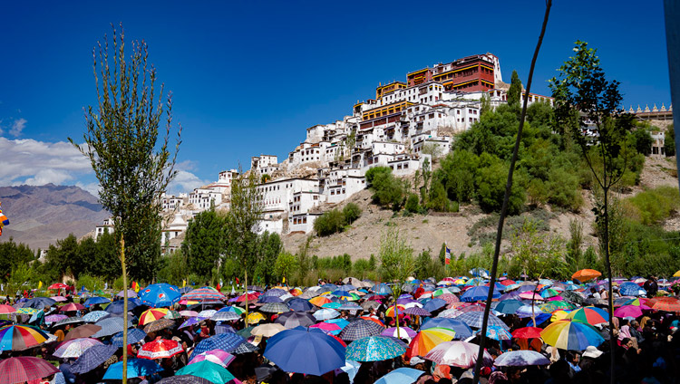 A view of Thiksey Monastery on the hill as many of the 2,500 people attending the ground breaking ceremony of the Library and Learning Centre use umbrellas to protect from the sun in Leh, Ladakh, J&K, India on July 29, 2018. Photo by Tenzin Choejor
