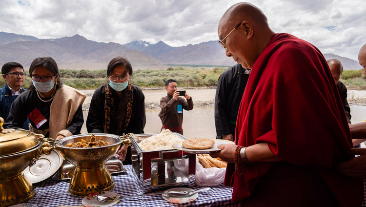 His Holiness the Dalai Lama serving himself during lunch organized by LAHDC at Sindhu Ghat in Leh, Ladakh, J&K, India on July 29, 2018. Photo by Tenzin Choejor