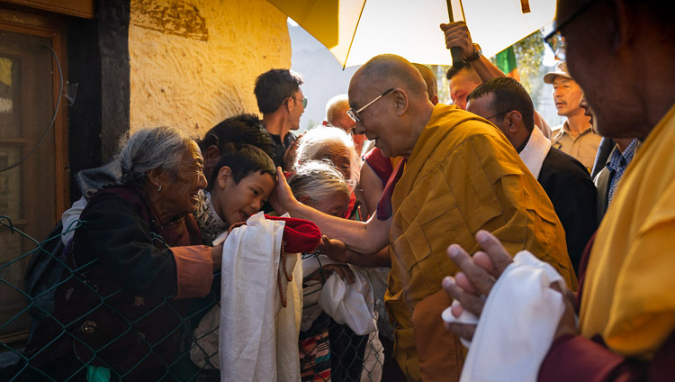 His Holiness the Dalai Lama greeting well-wishers as he walks from his residence to the Shiwatsel Teaching Ground in Leh, Ladakh, J&K, India on July 31, 2018. Photo by Tenzin Choejor