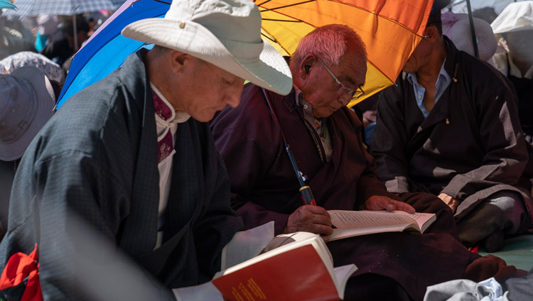 Members of the crowd following the text during His Holiness the Dalai Lama's final day of teachings in Leh, Ladakh, J&K, India on July 31, 2018. Photo by Tenzin Choejor