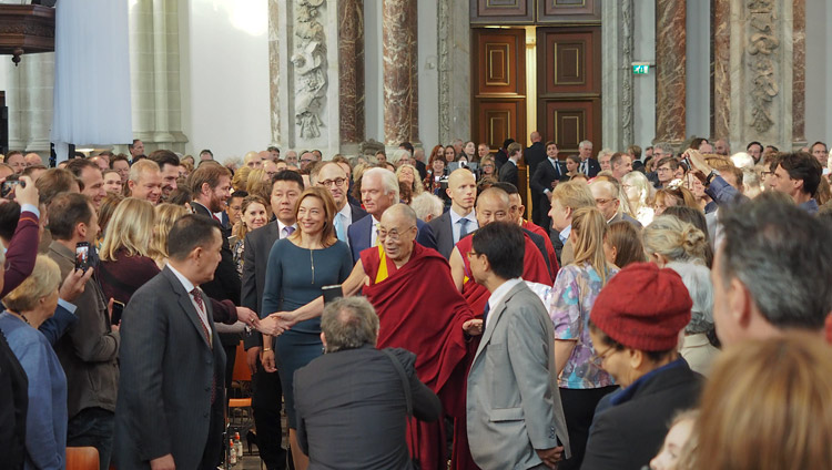 Escorted by the Nieuwe Kerk Director Cathelijne Broers His Holiness the Dalai Lama greets members of the audience on his arrival at the Nieuwe Kerk in Amsterdam, Netherlands on September 15, 2018. Photo by Jeremy Russell