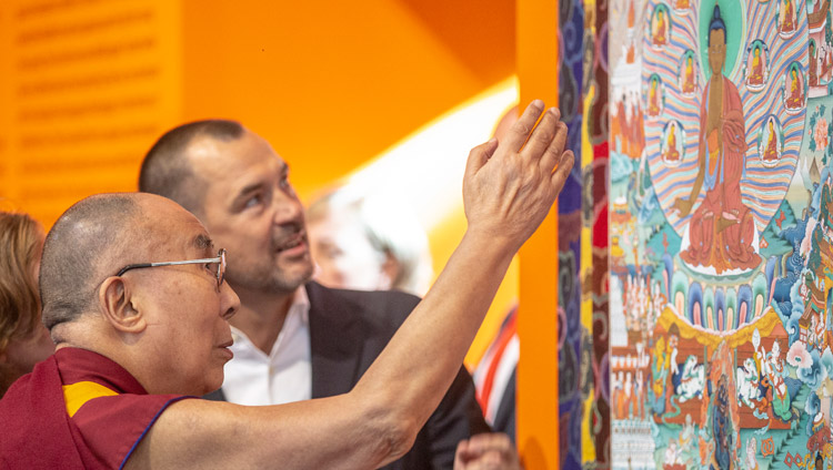 His Holiness the Dalai Lama looking at a thangka painting of the twelve deeds of the Buddha's life, part of the exhibit illustrating the 'Life of the Buddha' at Nieuwe Kerk in Amsterdam, Netherlands on September 15, 2018. Photo by Jeppe Schilder