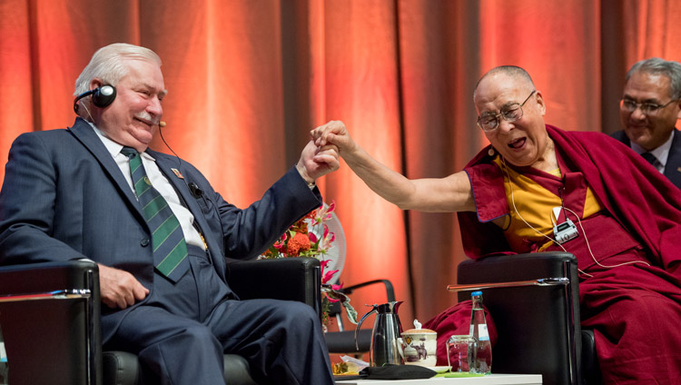 His Holiness the Dala Lama reaching out to clasp the hand of Lech Walesa, leader of the Solidarity movement and former President of Poland, during the discussion on non-violence in Darmstadt, Germany on September 19, 2018. Photo by Manuel Bauer