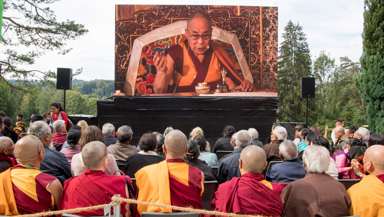 Members of the crowd watching His Holiness the Dalai Lama on a big screen outside the temple during the ceremony commemorating Tibet Institute Rikon's 50th anniversary in Rikon, Switzerland on September 21, 2018. Photo by Manuel Bauer