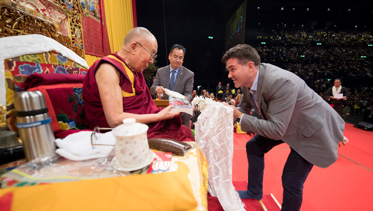 Daniel Aitken, President of Wisdom Books, requesting His Holiness to release the paperback edition of 'The Life of My Teacher: A Biography of Kyabjé Ling Rinpoché' at the conclusion of teachings at the Zurich Hallenstadion in Zurich, Switzerland on September 23, 2018. Photo by Manuel Bauer