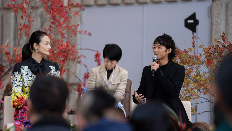 Fashion model Ai Tominaga looks on as film director Kenji Kohashi, both special guests, describes his experiences in Tibet as an introduction to His Holiness the Dalai Lama's talk in Tokyo, Japan on November 17, 2018. Photo by Tenzin Choejor