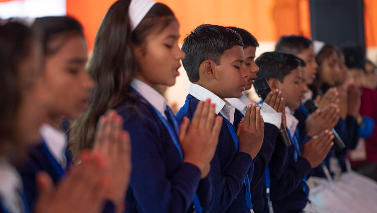 A group of local children in school uniform reciting the Mangala Sutta in Pali at the start of His Holiness the Dalai Lama's teaching in Sankisa, UP, India on December 3, 2018. Photo by Lobsang Tsering