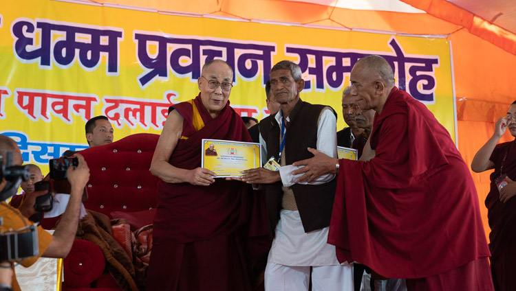 His Holiness the Dalai Lama presenting certificates of appreciation to the organizers of his three day teaching in Sankisa, UP, India on December 5, 2018. Photo by Lobsang Tsering
