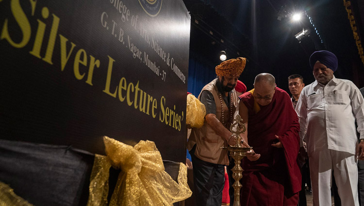 His Holiness the Dalai Lama joins in lighting a lamp to open the program at Guru Nanak College of Arts, Science & Commerce in Mumbai, India on December 13, 2018. Photo by Lobsang Tsering
