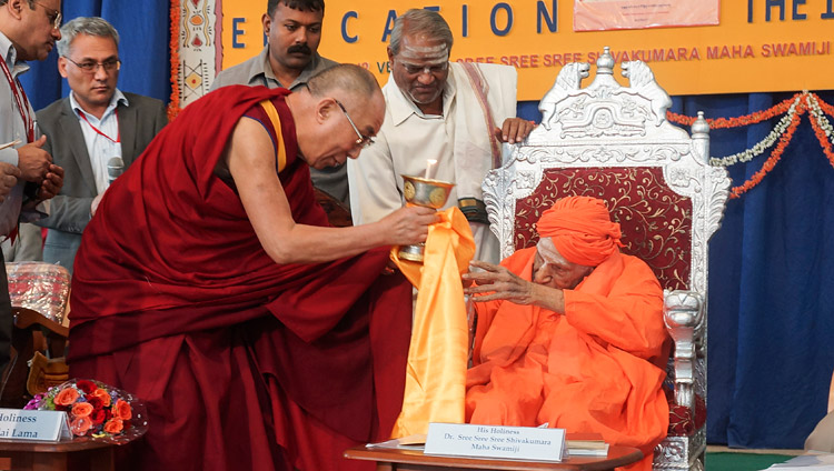 His Holiness the Dalai Lama offering a butter lamp to Sree Shivakumara Swamiji during his visit to Tumkur University in Tumkar, Karnataka, India on November 27, 2012. Photo by Jeremy Russell