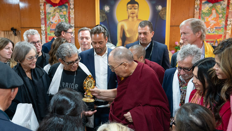 The audience gathers around His Holiness the Dalai Lama as he presents a Dharma Wheel to Deepak Chopra at the conclusion of their meeting in Dharamsala, HP, India on February 11, 2019. Photo by Tenzin Choejor