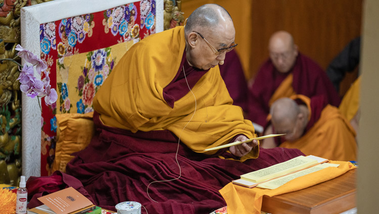 "His Holiness the Dalai Lama reading from Bhavaviveka's ""Essence of the Middle Way"" on the second day of his teachings in Dharamsala, HP, India on February 21, 2019. Photo by Tenzin Choejor"