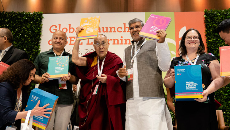 His Holiness the Dalai Lama with Delhi Deputy Chief Minister Manish Sisodia and Nobel Peace Laureate Kailash Satyarthi holding the SEE Learning curriculum text books in New Delhi, India on April 5, 2019. Photo by Tenzin Choejor