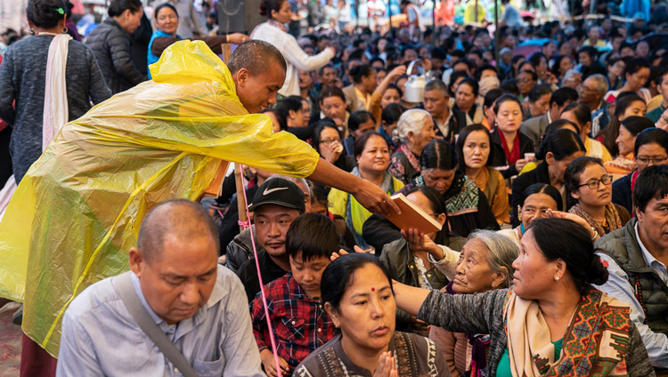 Volunteers handing out books to members of the audience on the second day of His Holiness the Dalai Lama's teachings in Manali, HP, India on August 14, 2019. Photo by Tenzin Choejor
