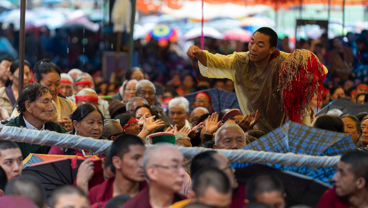 A volunteer passing out ritual protection cords as His Holiness the Dalai Lama gives the Empowerment of Mahakarunika Lokeshvara in Manali, HP, India on August 17, 2019. Photo by Tenzin Choejor