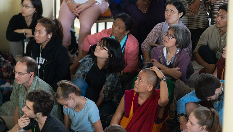Members of the audience sitting on the veranda outside the Main Tibetan Temple watching His Holiness the Dalai Lama on a TV screen during the first day of his teachings in Dharamsala, HP, India on September 4, 2019. Photo by Tenzin Choejor