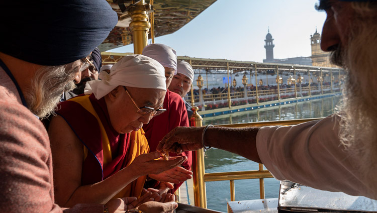 His Holiness the Dalai Lama receiving 'prasad', blessed food, that is offered to each pilgrim as he leaves the Darbar Sahib at the the Golden Temple in Amritsar, Punjab, India on November 9, 2019. Photo by Tenzin Choejor