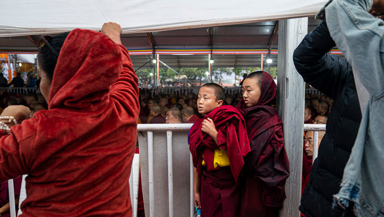 Young monks finding protection from the rain during as His Holiness the Dalai Lama addresses the crowd before conducting an Avalokiteshvara Empowerment at the Kalachakra Ground in Bodhgaya, Bihar, India on January 3, 2020. Photo by Tenzin Choejor