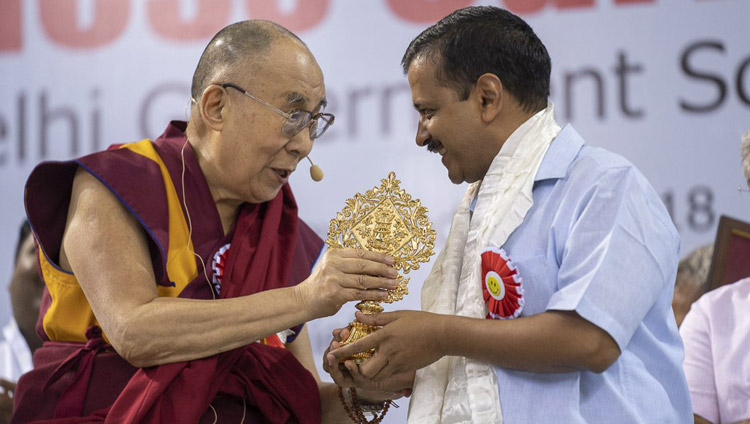 His Holiness the Dalai Lama presenting Delhi Chief Minister Arvind Kejriwal with an auspicious emblem at the conclusion of the launch of the Happiness Curriculum in Delhi Government Schools at Thyagraj Stadium in New Delhi, India on July 2, 2018. Photo by Tenzin Choejor