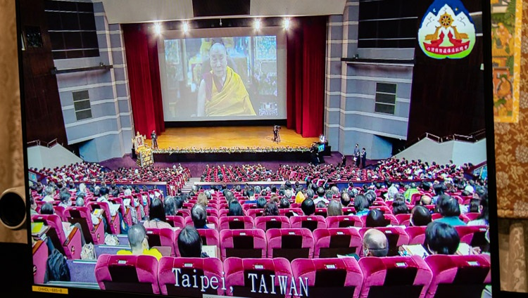 A view of the hall in Taipei, Taiwan shown on a TV screen in front of His Holiness the Dalai Lama during the third day of his virtual teachings from his residence in Dharamsala, HP, India on October 4, 2020. Photo by Ven Tenzin Jamphel
