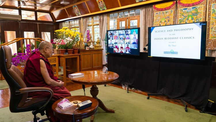 His Holiness the Dalai Lama looking at a close up of the newly released English translation of the second volume of the series Science and Philosophy in the Indian Buddhist Classics on a TV at his residence in Dharamsala, HP, India at the start of the virtual book launch on November 13, 2020. Photo by Ven Tenzin Jamphel