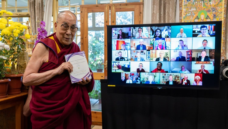 "His Holiness holding a copy of ""Science and Philosophy in the Indian Buddhist Classics, Vol. 2 - The Mind"" as he stands in front of the TV displaying the faces of the various contributors at his residence in Dharamsala, HP, India on November 13, 2020. Photo by Ven Tenzin Jamphel"