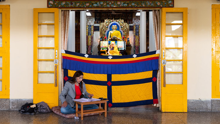 The Portuguese interpreter sitting outside the Main Temple translating His Holiness the Dalai Lama's live teaching in Dharamsala, HP, India on May 16, 2020. Photo by Lobsang Tsering