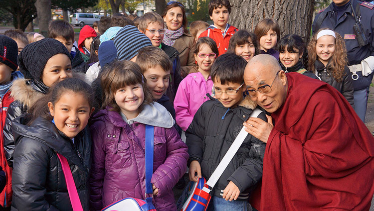 His Holiness the Dalai Lama stops to talk to a group of school children on his way to the Provincial Offices in Bolzano, South Tyrol, Italy, on April 10, 2013.(Photo by Jeremy Russell/OHHDL)